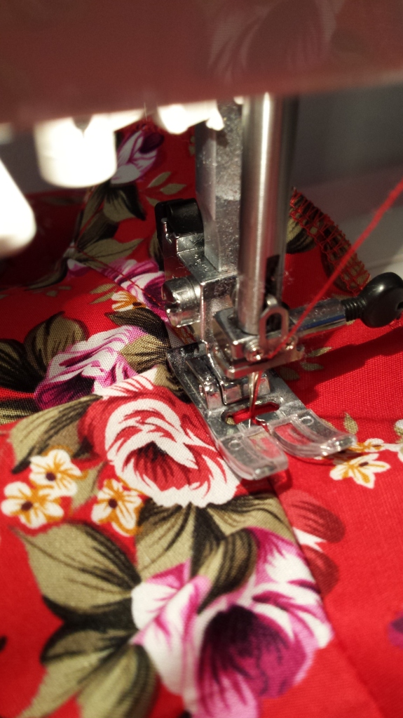 The stitching is on the facing, close to the seam line, and it holds the seam allowance (underneath) in place